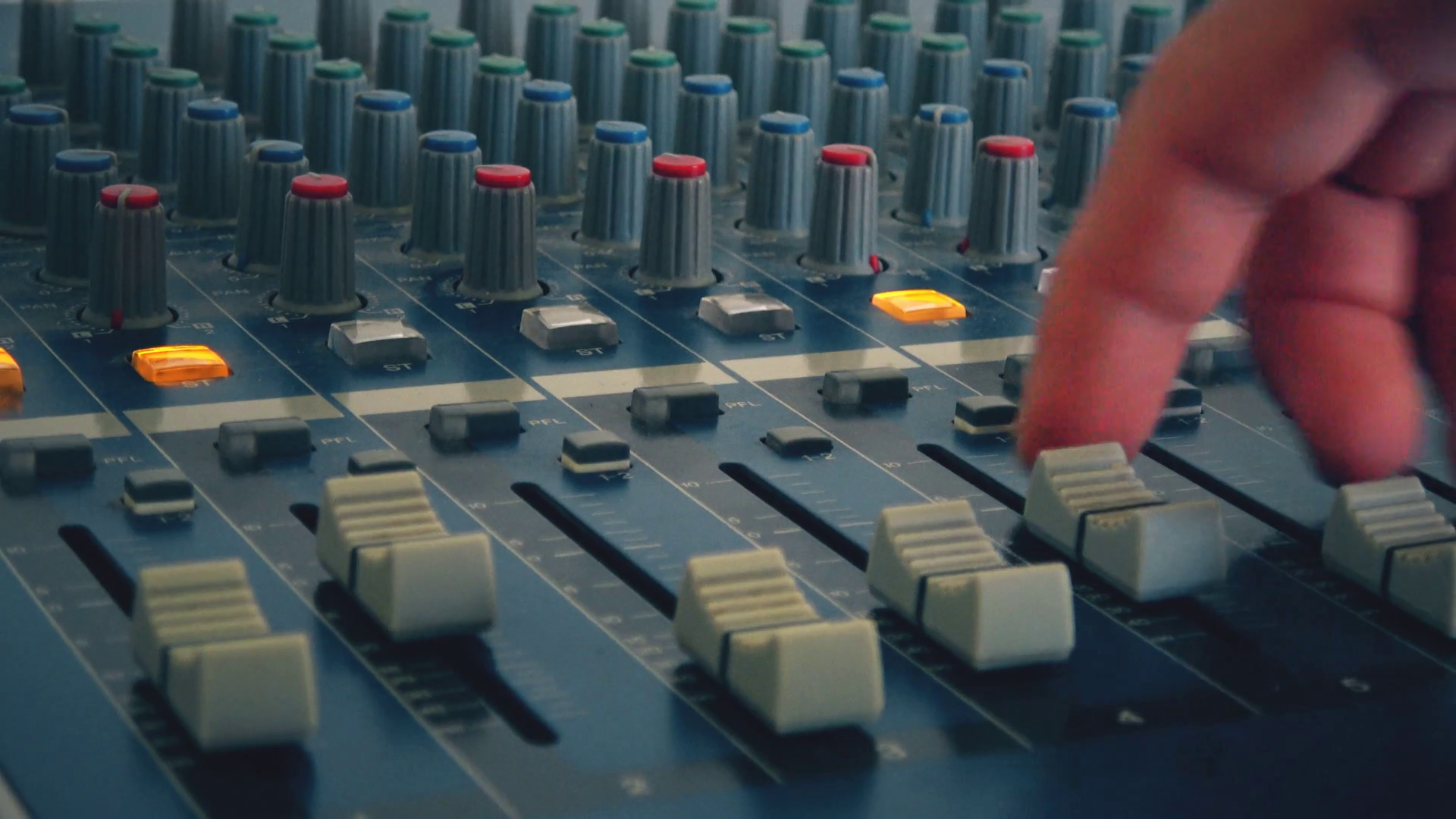 image of someone moving faders on the control surface